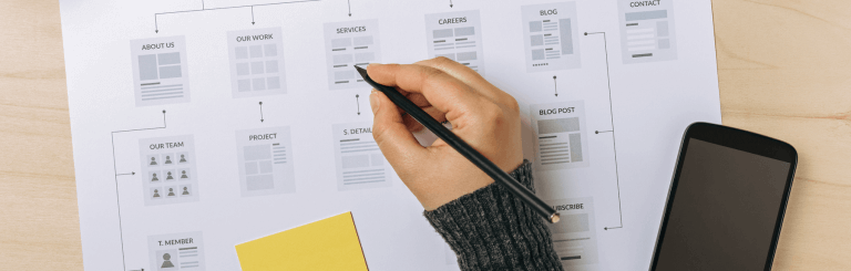 person-writing-on-paper-wireframes